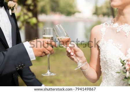 Bride and Groom toasting. Champagne glasses. Horizontal format. Close up picture.