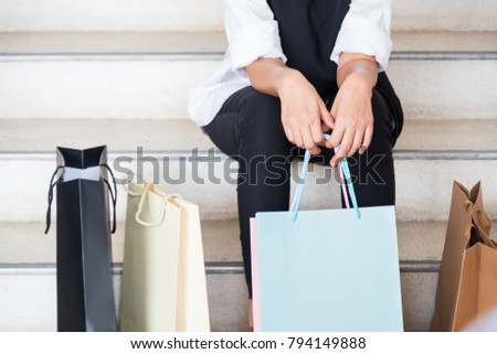 Woman sit at the stair with shopping bag after shopping all day and she was tired. #794149888