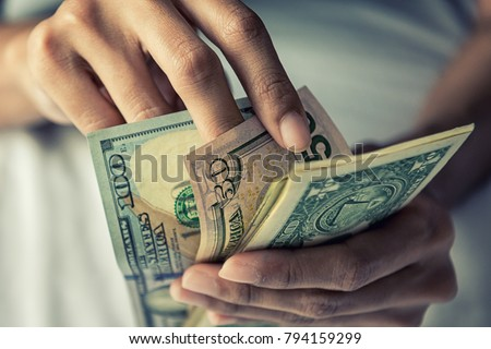 Close-up Hands counting money American dollars , Counting money American dollars with hand , Vintage tone effect , Income and Business concept.