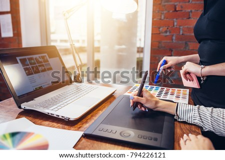 Close-up image of women drawing a project using a graphic tablet and a laptop sitting in modern office #794226121