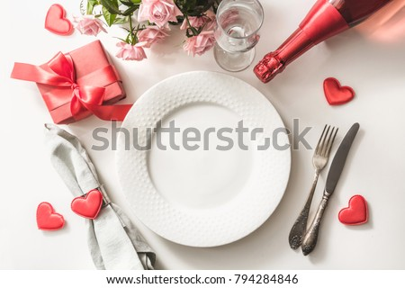 Valentines day dinner with table place setting with red gift, glass for champagne, a bottle of champagne, pink roses, hearts with silverware on white background. View from above. Valentine's card. #794284846