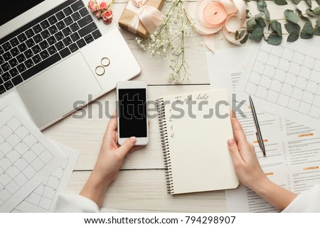 Wedding arrangement background. Female hands preparing for marriage, using laptop, smartphone, paper calendars and planners, top view. Bridal wallpaper with copy space on to do list #794298907