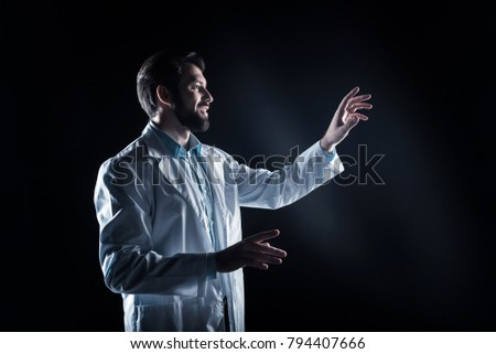 Lab worker. Delighted positive bearded man wearing a labcoart and using modern technology while working in the lab #794407666