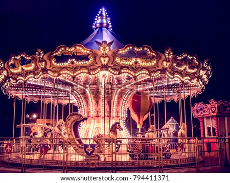 beautiful bright carousel in park at night in winter Royalty-Free Stock Photo #794411371