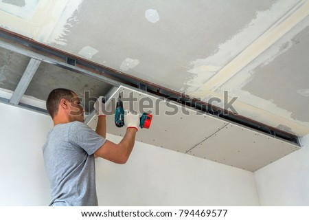 Construction worker assemble a suspended ceiling with drywall and fixing the drywall to the ceiling metal frame with screwdriver. Renovation, construction and do it yourself DIY concept. #794469577