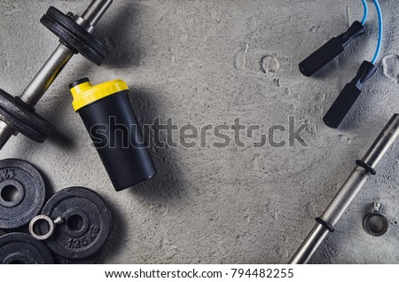 Fitness or bodybuilding concept background. Product photograph of old iron dumbbells on grey, conrete floor in the gym. Photograph taken from above, top view with lots of copy space #794482255