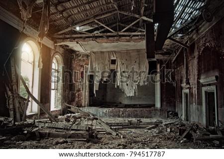 Old creepy abandoned rotten ruined haunted theater, a ragged curtain, Sukhum, Abkhazia Royalty-Free Stock Photo #794517787
