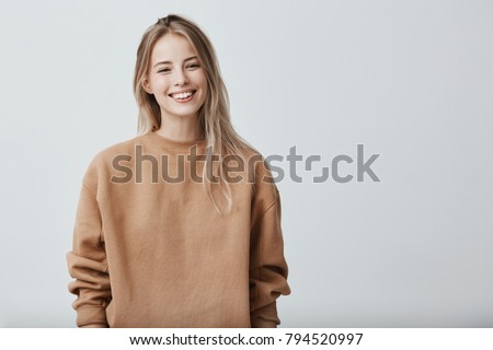 Cheerful positive female youngster with blonde hair, dressed casually, glad to receive graduation congratulations from friends, starting new stage in life. Positive emotions and feelings #794520997
