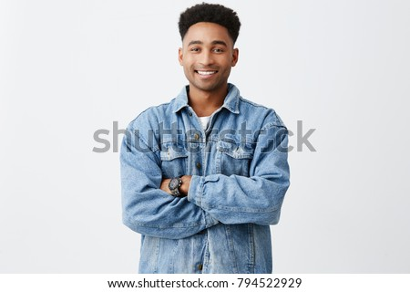 Isolated portrait of young funny dark-skinned man with arms crossed with afro hairstyle in casual white shirt under denim jacket with excited face expression #794522929