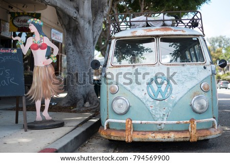 Encinitas, California, USA, August, 1st 2016, a classic Volkswagen Bus sits on the street next to a hula girl sign in the beach community of Encinitas CAlifornia,  #794569900