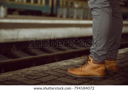 mans legs close up stand at the railway station railroad on background #794584072