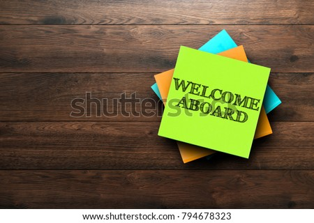 Welcome Aboard, the phrase is written on multi-colored stickers, on a brown wooden background. Business concept, strategy, plan, planning. Royalty-Free Stock Photo #794678323