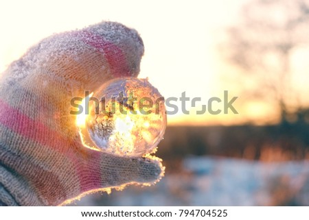 hand in mittens holding transparent ball (sphere) with reflection. winter time concept. beautiful nature winter landscape. christmas and new year wonderful season #794704525