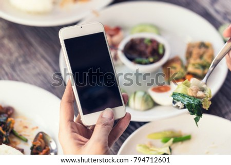 Close up of man hand using or looking at his a smartphone and having lunch in the restaurant.