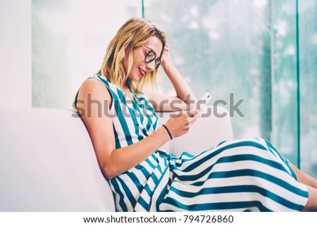 Side view of smiling fashionable blonde female in stylish eyeglasses messaging in online chat via high speed free 4G internet connected to modern smartphone gadget sitting on comfortable sofa at home #794726860