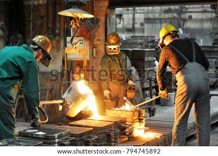 Group of workers in a foundry at the melting furnace - production of steel castings in an industrial company  #794745892