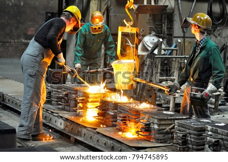 Group of workers in a foundry at the melting furnace - production of steel castings in an industrial company  #794745895