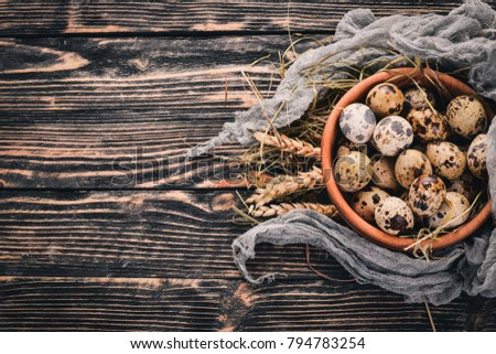 Quail eggs in a wooden bowl. On a wooden background. Top view. Copy space. #794783254