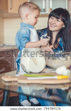 mother whisking dough and son holding dough mold #794789176