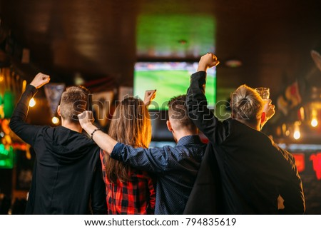 Friends watches football on TV in a sport bar #794835619