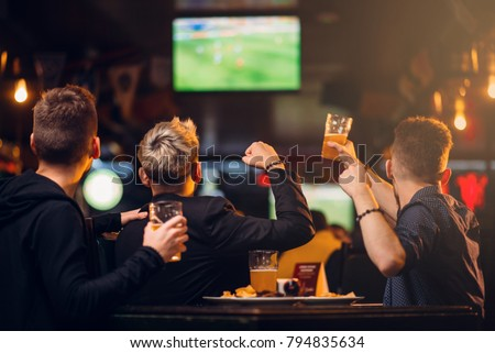 Three men watches football on TV in a sport bar Royalty-Free Stock Photo #794835634