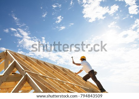 male roofer carpenter working on roof structure on construction site #794843509