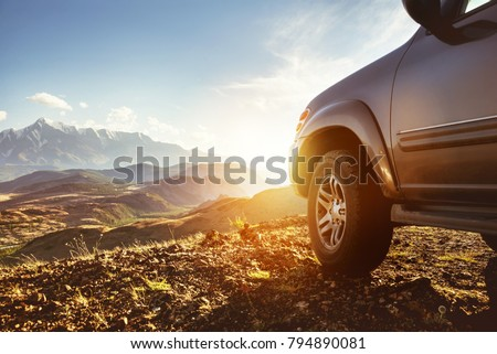 Travel concept with big 4x4 car against sunset and mountains. Closeup photo of offroad wheel #794890081