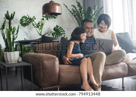 Young Asian family looking at the laptop together at home. #794913448