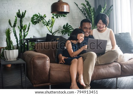 Young Asian family looking at the laptop together at home. #794913451