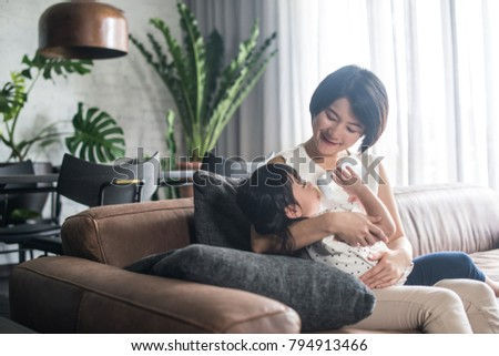 Young happy Asian mother feeding milk to daughter at home. #794913466