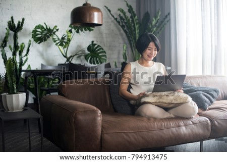 Young happy Asian woman using the computer at home. #794913475