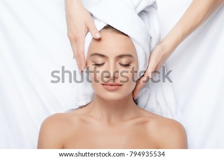 Cute  girl with thick eyebrows and perfect skin at white background, towel on head, beauty photo concept, skin care, spa concept, doing facial massage, stress free. #794935534