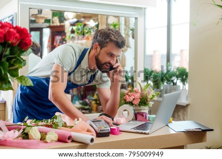 Male florist talking on the phone and receiving an order, making notes in his laptop. Man works in his own flower shop.