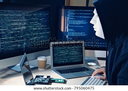Masked man hacking server in dark room #795060475