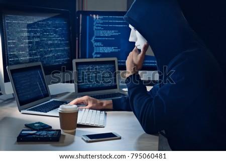 Masked man hacking server in dark room #795060481