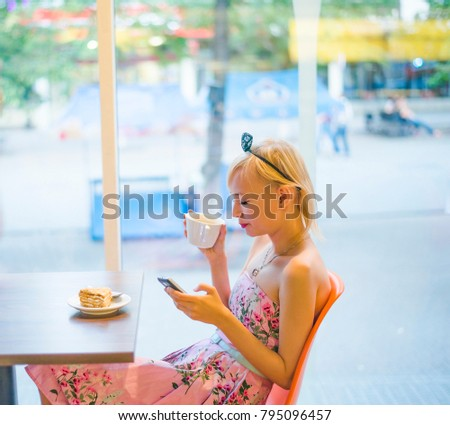 blond woman talking on the phone in cafe and looking to screen of mobile phone. honey cake and coffee on the table. Bright sunny morning in cafe.  #795096457
