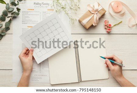 Wedding background with checklist and calendar. Female hands arranging marriage, filling in planners on white wooden table with lots of tender bridal stuff, top view #795148150