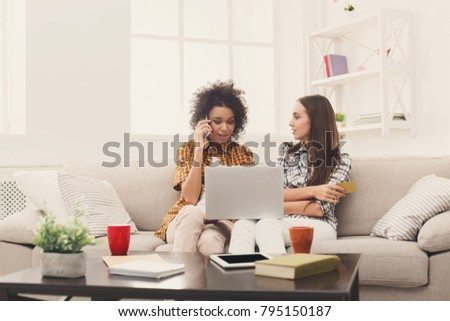 Two happy women shopping online with credit card and laptop sitting on sofa at home and making order by mobile phone, copy space #795150187