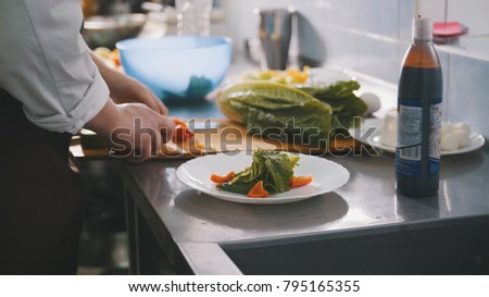 Male chef preparing salad in commercial kitchen #795165355