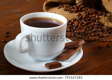 A white pitcher, coffee beans, chocolate and a coffee bag with a wooden background #795167281