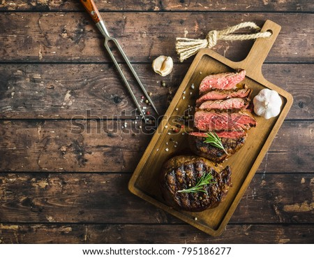 Sliced grilled marbled meat steak Filet Mignon, seasonings, fork, wooden cutting board. Space for text. Juicy meat steak. Beef steak grilled/fried. Top view. Roasted meat steak. Close-up. Rustic #795186277