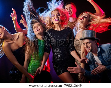 Dance party with group people dancing. Women and men have fun in night club. Happy girl with tousled hair on foreground. Back light on girls hair. Rest after hard day at work. #795213649