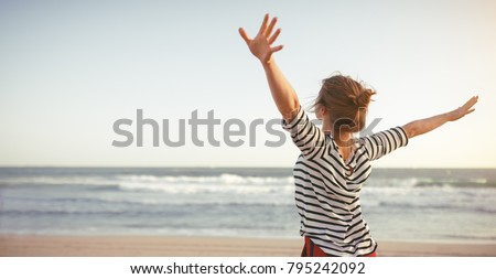 happy young woman enjoying freedom with open hands on sea Royalty-Free Stock Photo #795242092