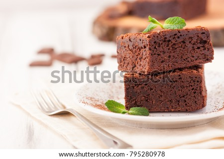 Chocolate brownie square pieces in stack on white plate decorated with mint leaves and cocoa powder on white vintage wooden background. American traditional delicious dessert. Close up photography. #795280978