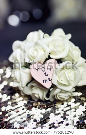 Image of Valentine's day or wedding composition with small pink wooden heart and bouquet of white roses