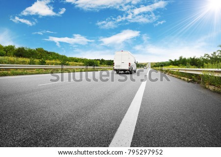 Big white van on the countryside road shipping goods against blue sky with sun #795297952