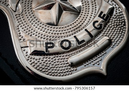 "Cops and police officer badge with macro close up on the ""police"" text of a  cop badge"