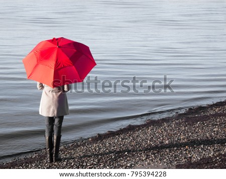 Woman holding a red umbrella walking on a rainy day at a beach.  #795394228