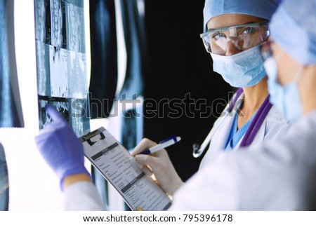 Two female women medical doctors looking at x-rays in a hospital. #795396178