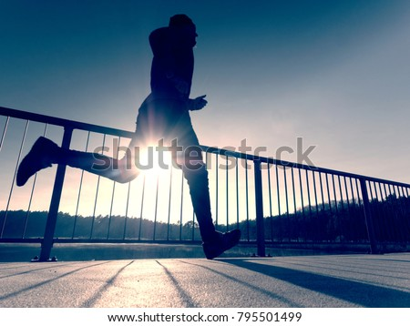 Rear view to runner in blue t-shirt and black leggings  running on bridge. Outdoor exercising on smooth concrete ground on lake bridge. Sun is outlining man body #795501499